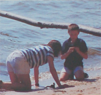 Photo of a mother and her son looking for shells on the beach